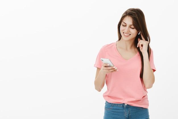 Brünette frau posiert im studio mit ihrem telefon und ohrhörern
