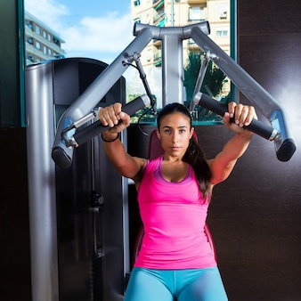 Brünette frau sitzt brust presse maschine fitnessstudio