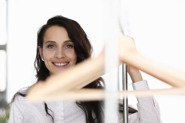 Brünette frau steht lächelnd auf hintergrund von kleiderbügeln