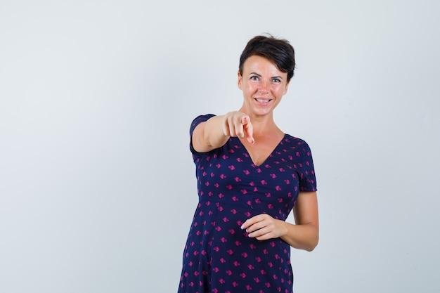 Brünette frau zeigt mit ihren zeigefingern in lila und rot gemustertem kleid und schaut glücklich, vorderansicht.