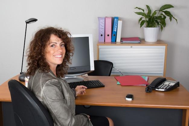 Brünette geschäftsfrau an ihrem schreibtisch im büro