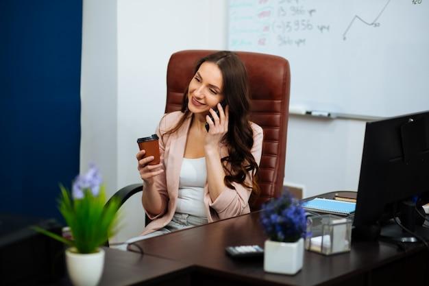 Brünette geschäftsfrau, die auf smartphone chattet