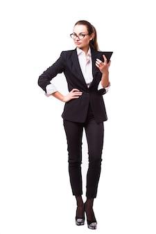Brünette geschäftsfrau, die ebook tablett-pc-notizbuch und blauen anzug auf weiß liest