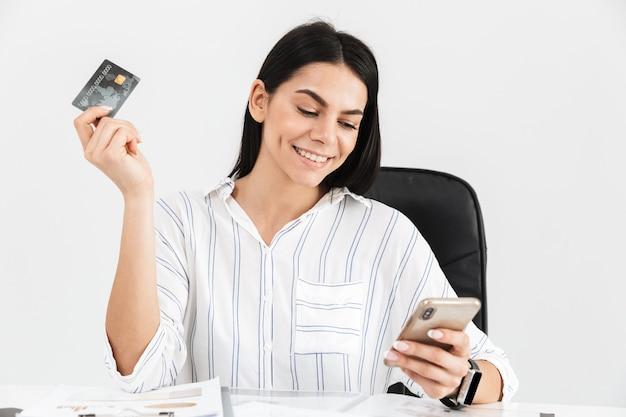 Brünette geschäftsfrau, die smartphone und plastikkreditkarte beim sitzen im sessel am tisch im büro lokalisiert über weißer wand hält