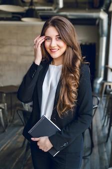 Brünette geschäftsfrau mit welligen langen haaren und blauen augen steht mit einem notizbuch in den händen und lächelt breit
