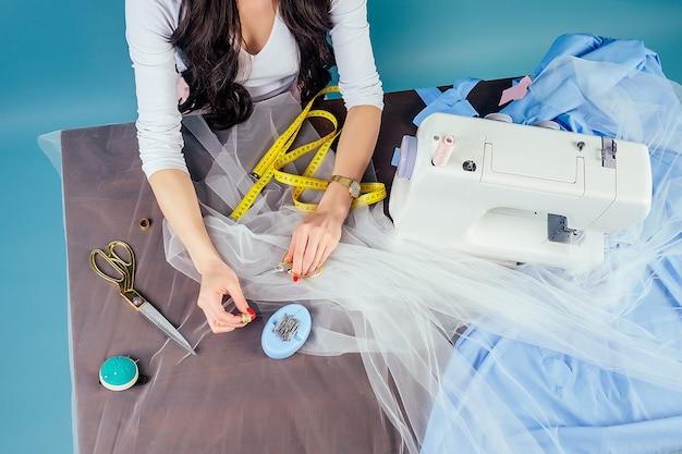 Brünette geschäftsfrau schneiderin (schneiderin) arbeitet im atelier mit nähmaschine und maßband auf blauem hintergrund im studio.