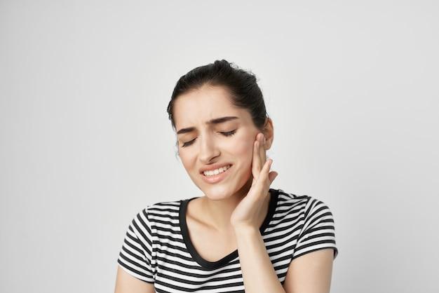 Brünette hält an zahnschmerzen gesundheitswesen isolierten hintergrund gesicht. foto in hoher qualität