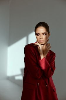 Brünette helle make-up hände nahe gesicht rote jacke mode glamour hellen hintergrund