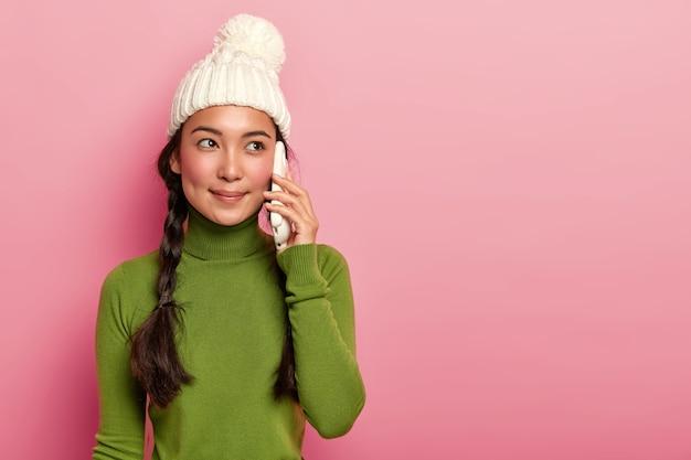 Brünette hipster frau, die über modernes gadget auf rosa hintergrund anruft