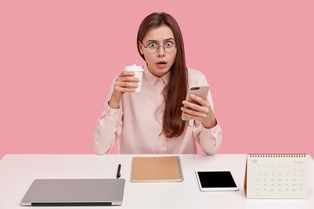 Brünette hübsche junge bloggerin liest empfangene benachrichtigung auf handy, hat ausdruck überrascht