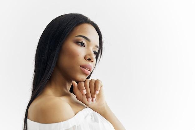 Brünette im weißen kleid posiert für kosmetikmode
