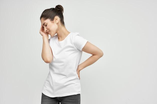 Brünette im weißen t-shirt, die ihre unzufriedenheit mit den gesundheitsproblemen der bauchmenstruation hält
