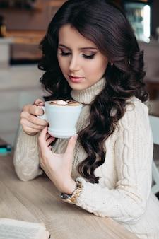 Brünette in einem café trinkt tee, isst süßigkeiten, liest ein buch, schaut auf die tasse, schöne augen und wunderschönes make-up, welliges haar. ausruhen nach einem tag voller freude am leben. glückliches mädchen. weiche warme farben.