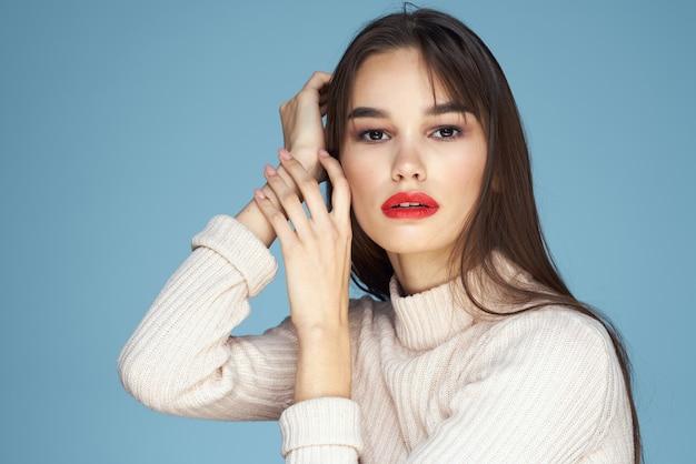 Brünette in einem weißen pullover rote lippen bezaubern langes haar blau