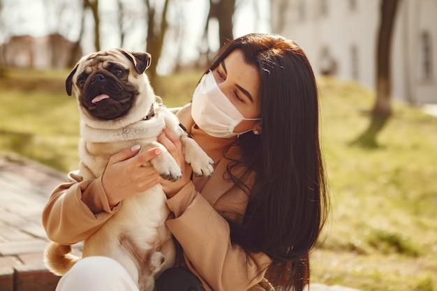 Brünette in einer maske geht mit mops