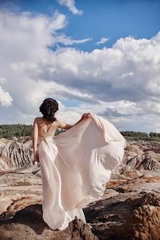 Brünette in rosa kleid steht auf einer klippe, der wind kräuselt ein kleid