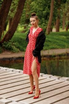 Brünette in stilvoller kleidung zum feiern und spazierengehen. park im sommer. modell in einem roten sommerkleid, jacke, schuhe.