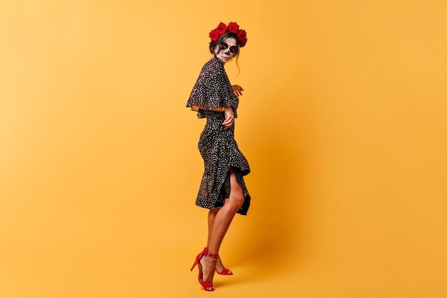 Brünette in voller länge mit nach hinten gepinntem haar in wunderschönem outfit und roten sandalen. dame bereitet sich auf halloween vor