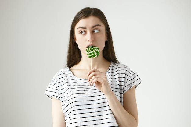 Brünette junge frau auf strenge diät lecken bunte gelbgrüne lutscher im geheimen, seitwärts schauen, sich besorgt fühlen, erwischt zu werden, ungesunde zucker-bonbons zu essen