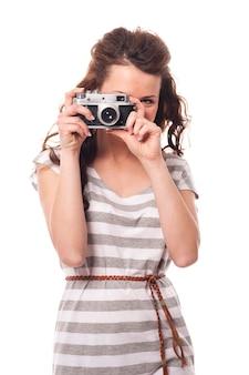 Brünette junge frau, die foto durch retro-kamera nimmt