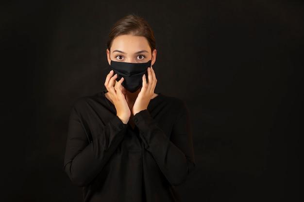 Brünette junge frau, die ihr gesicht in der schutzmaske berührt.