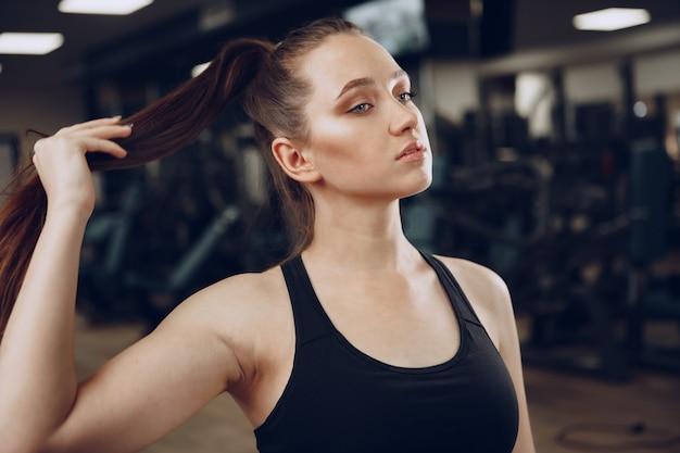 Brünette junge frau, die müde in einem fitnessstudio nach dem training sitzt