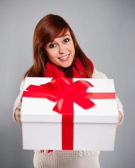 Brünette junge frau, die weißes weihnachtsgeschenk mit rotem band gibt