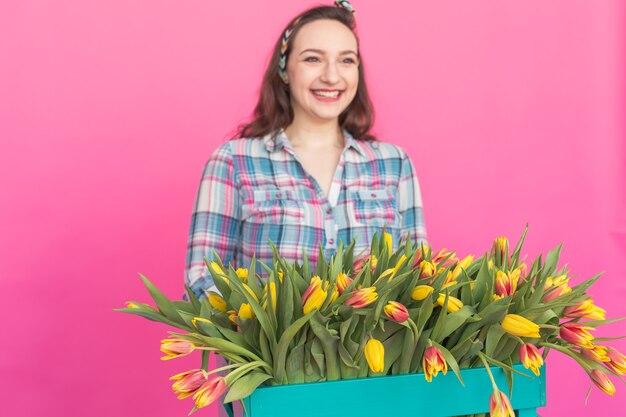 Brünette junge frau im studio mit bündel tulpen auf rosa oberfläche