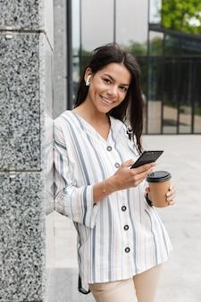 Brünette junge frau in freizeitkleidung, die kaffee zum mitnehmen trinkt und das handy hält, während sie über dem gebäude steht