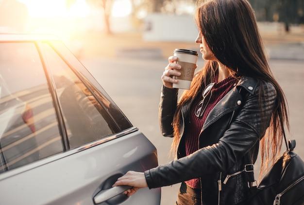 Brünette junge frau mit smartphone und tasse schwarzen kaffees nahe nagelneuem auto am stadtparkplatz