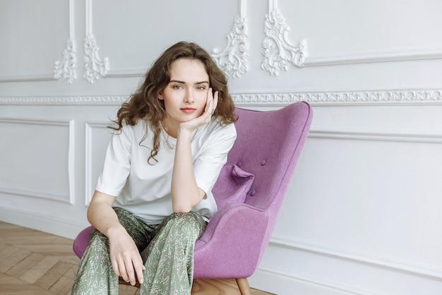 Brünette junge frau modell sitzt auf einem stuhl posiert in einer neuen kollektion von kleidung