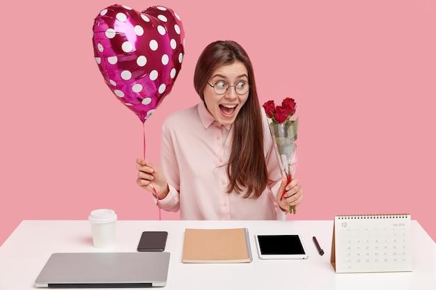 Brünette junge kaukasische frau, die herzförmigen ballon und strauß der roten rosen hält