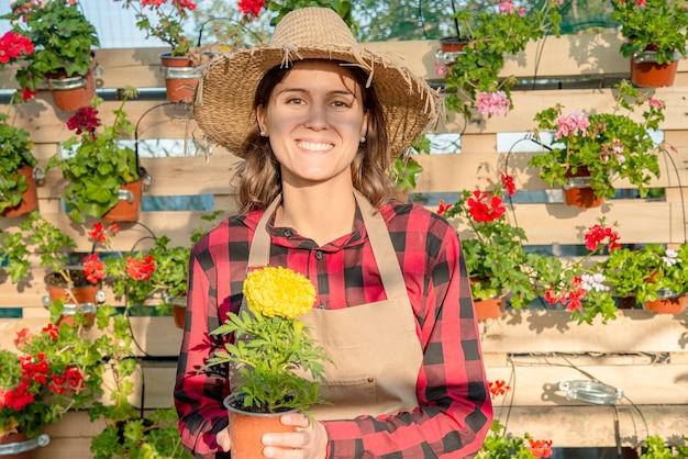 Brünette junge lächelnde gärtnerin in einem blumenladen