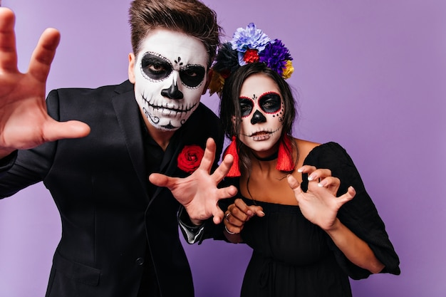 Brünette junge leute, die lustige gesichter während des halloween-fotoshootings machen. raffinierte freunde, die spaß auf der party in zombiekostümen haben.