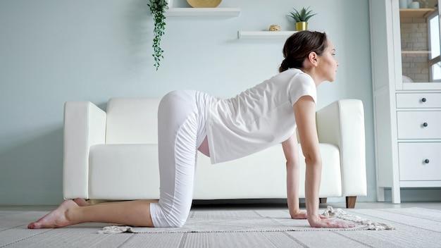 Brünette junge schwangere dame praktiziert marjaryasana yoga-position auf dem bodenteppich in der nähe des sofas in einem geräumigen zimmer in der seitenansicht, kamera-zoom