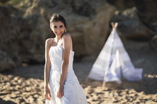 Brünette kaukasische braut, die lächelt, während sie am strand aufwirft