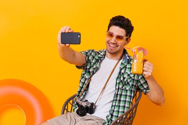 Brünette kerl im grünen hemd nimmt selfie und hält orange cocktail. porträt des mannes mit retro-kamera, die auf isoliertem raum mit aufblasbarem kreis aufwirft.