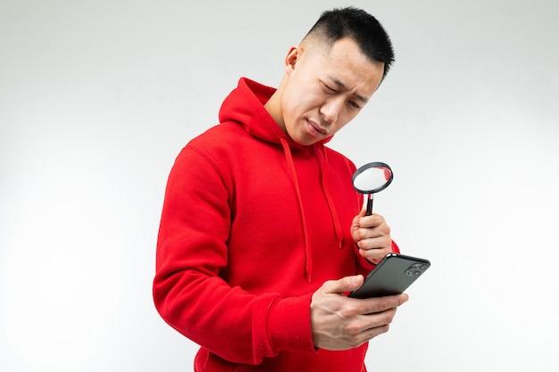Brünette kerl in einem roten pullover betrachtet das telefon durch eine lupe auf einem weißen hintergrund.