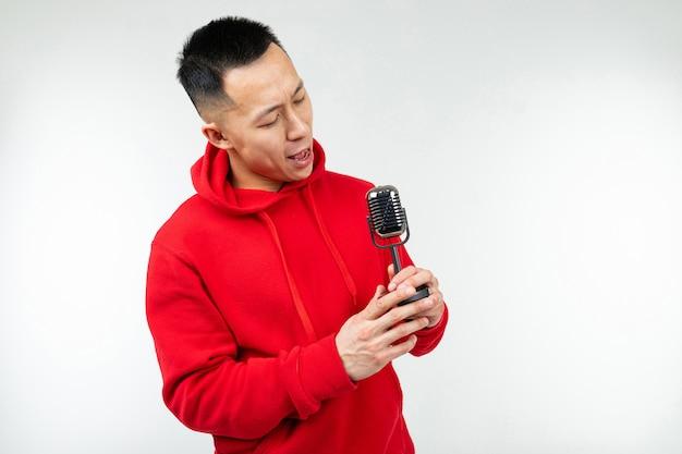 Brünette kerl in einem roten pullover singt in ein retro-mikrofon auf einem weißen hintergrund