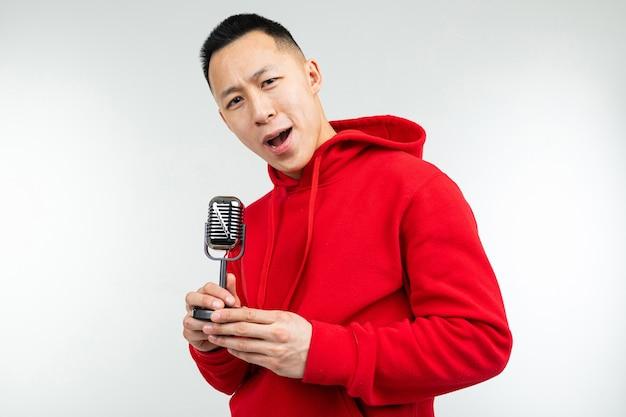 Brünette kerl in einem roten pullover singt in ein retro-mikrofon auf einem weißen hintergrund.