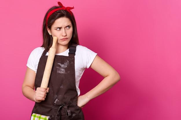Brünette köchin mit rotem haarband, mit mehl verschmutzter brauner schürze und weißem t-shirt entscheidet, welches rezept zum backen von kuchen verwendet wird. junger bäcker hält nudelholz und berührt damit die wange. kulinarisches konzept.