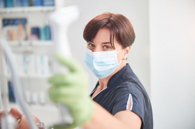 Brünette kosmetikerin in einer gesichtsmaske, die ein gerät für anti-aging-verfahren hält und in die kamera schaut