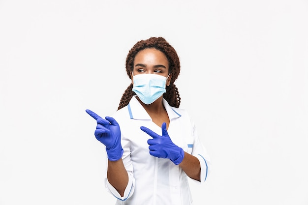 Brünette krankenschwester mit medizinischer gesichtsmaske und einweghandschuhen, die mit den fingern auf den kopierraum zeigt, der gegen weiße wand isoliert ist?