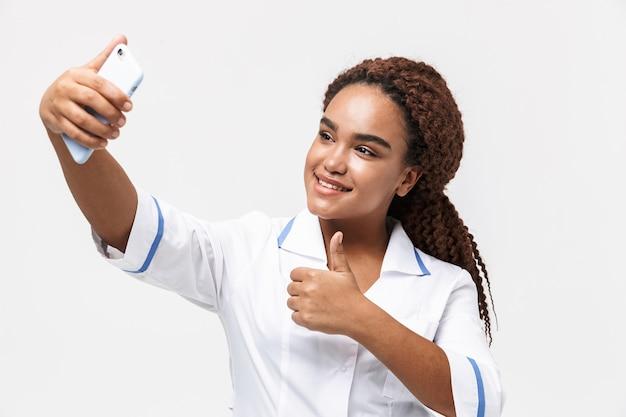 Brünette krankenschwester trägt medizinischen mantel hält und macht selfie-foto auf dem handy isoliert gegen weiße wand