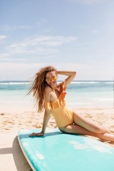 Brünette lachende dame, die am strand nach dem surfen aufwirft. prächtiges mädchen in der orangefarbenen badebekleidung, die auf sand sitzt und lächelt.