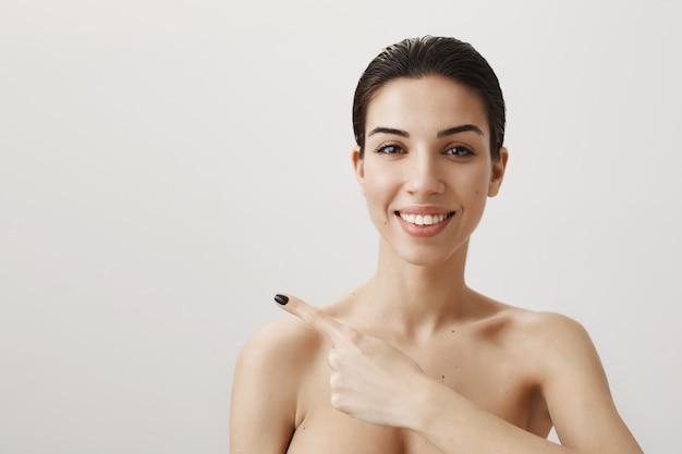 Brünette lächelt, steht nackt und zeigt mit dem finger nach links
