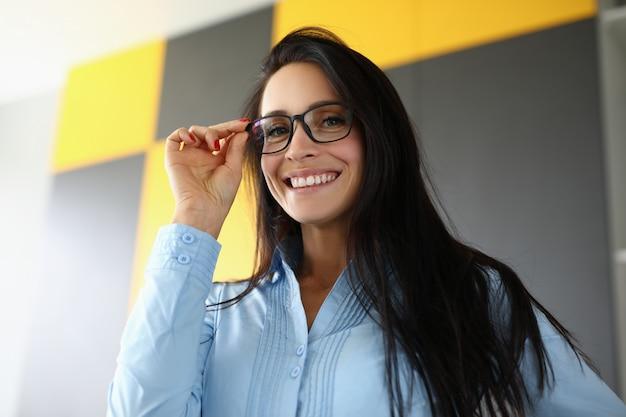 Brünette lächelt und hält hand für brille nahaufnahme