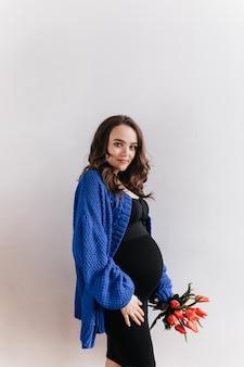 Brünette lockige schwangere frau in der blauen strickjacke hält blumenstrauß. charmante dame im schwarzen kleid wirft mit tulpen auf lokalisiertem hintergrund auf.