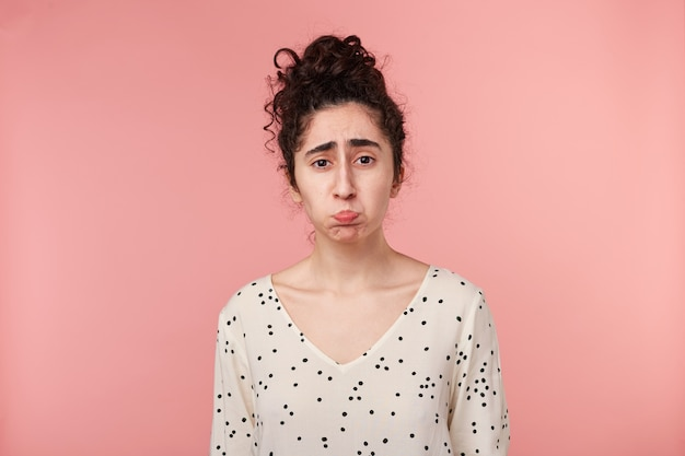 Brünette mädchen beleidigt traurig verärgert, schmollte ihre wangen ist überwältigt von negativen emotionen, schlecht gelaunt in bluse mit tupfen gekleidet, wird weinen, isoliert auf rosa