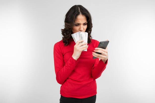 Brünette mädchen hält betrachtet ihr verdientes geld in ihren händen auf einem weißen hintergrund mit kopienraum.